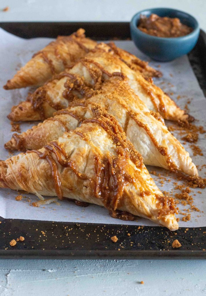 Four apple biscoff turnovers are laid out on a baking tray. They are drizzled with a lotus biscoff glaze, and topped with crushed Biscoff biscuits.