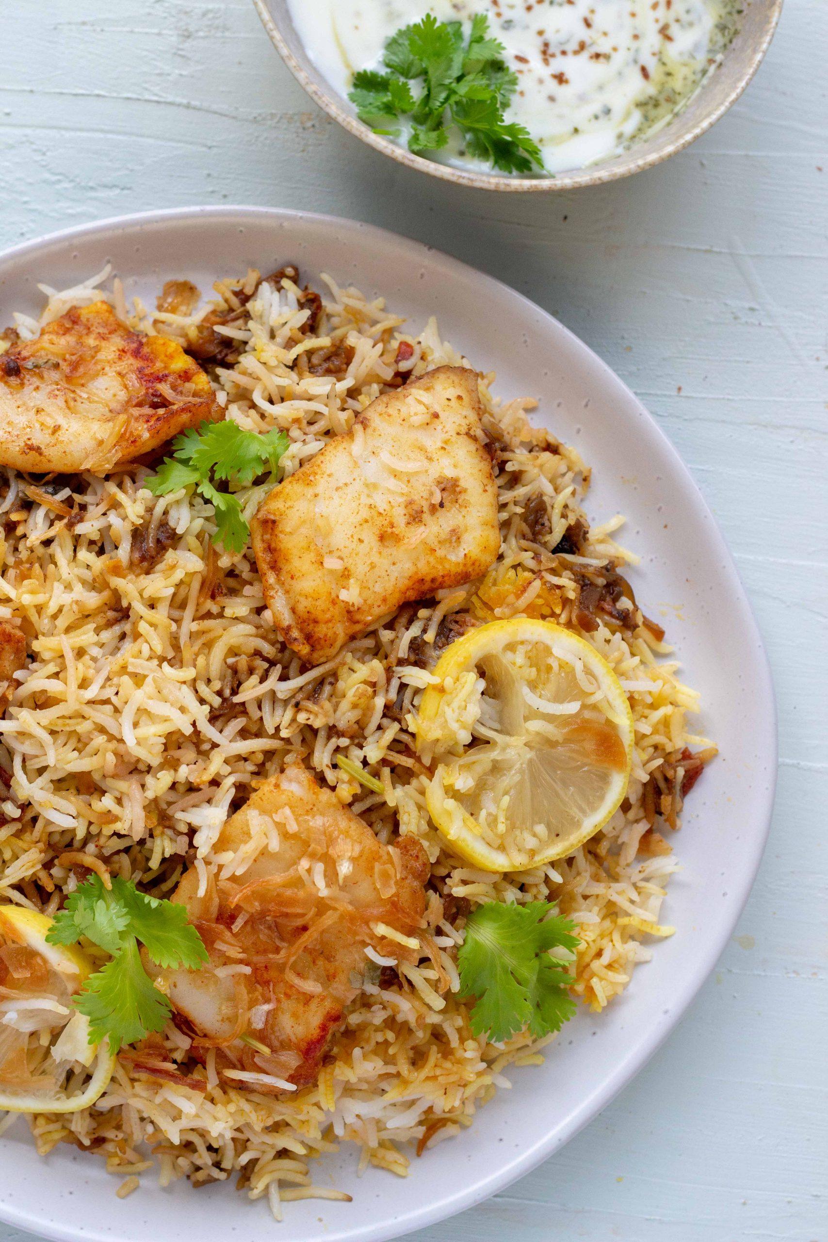 A plate of Pakistani style fish biryani with raita in the background.
