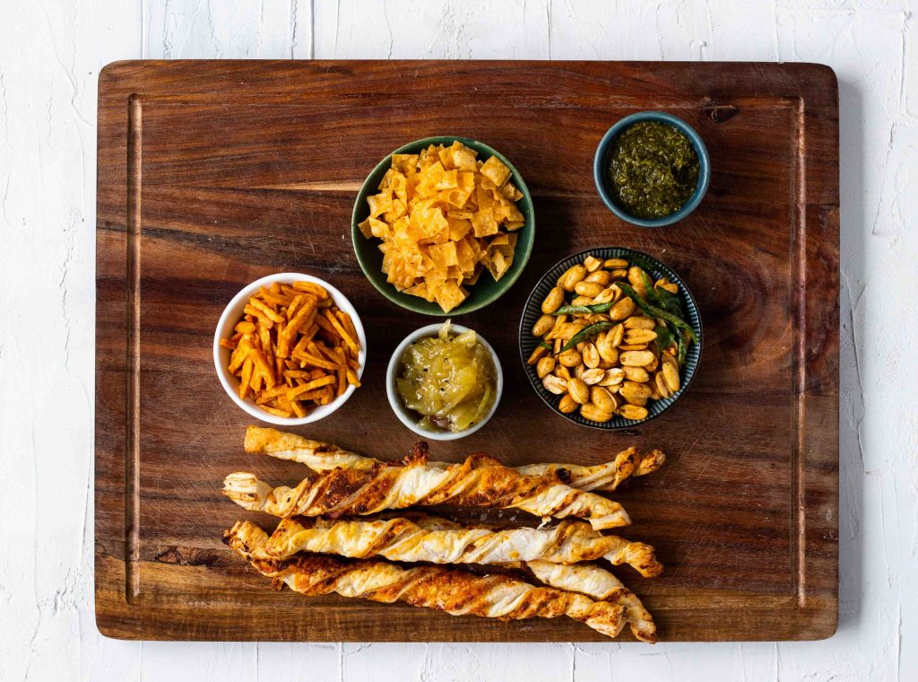 Assortment of Pakistani Indian snacks to add to a cheese board - from the left there are chili chips, paapri, mango chutney, green chutney, masala peanuts and puff pastry twists.