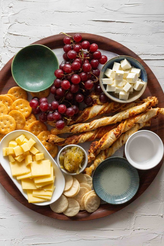 Setting out elements for a cheese board. There's Ritz crackers, rice crackers, cubed and sliced cheddar along with puff pastry straws, grapes, mango chutney and cubed feta.
