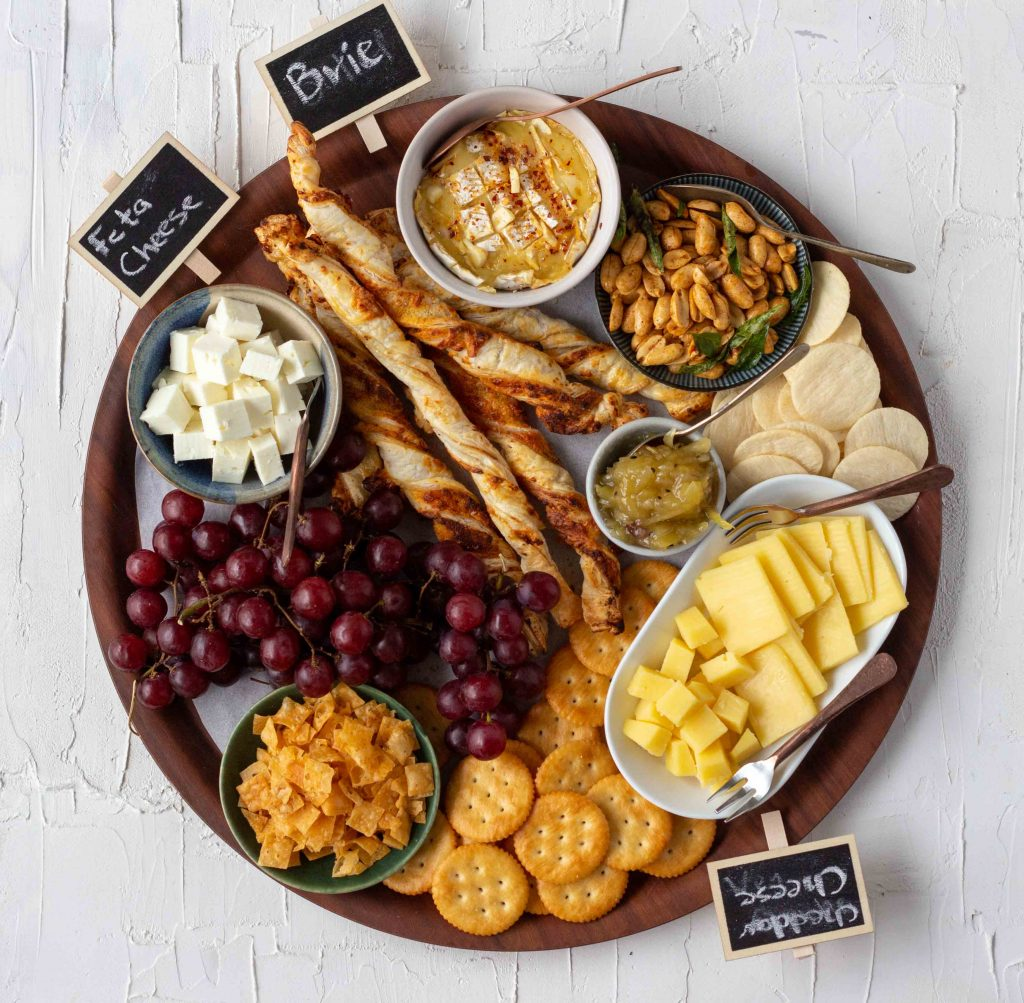 A cheese board set out for South Asians. Clockwise from the top there's cubed feta cheese, puff pastry straws, baked brie, masala peanuts, rice crackers, cubed and sliced cheddar cheese, ritz crackers, papri crisps, grapes, and mango chutney.