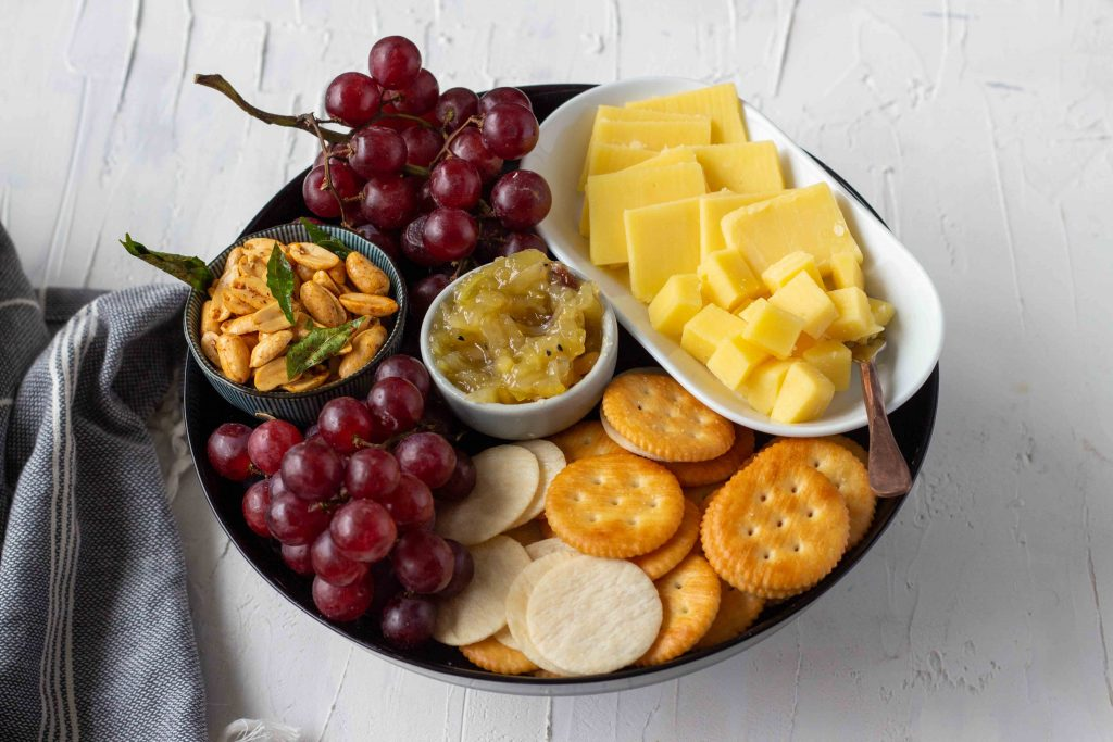 A small cheese board for around 4 people - the cheese board has grapes, masala peanuts, crackers, cubed and sliced cheddar, and mango chutney.