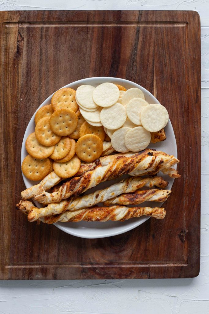 Selection of breads and crackers for a cheese board. There's Ritz crackers, rice crackers and puff pastry twists.