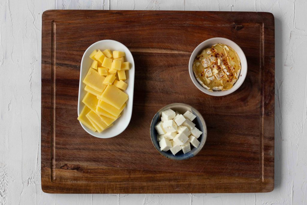 Selection of cheeses for a cheese board - cubed and sliced cheddar, feta cheese, and baked brie.