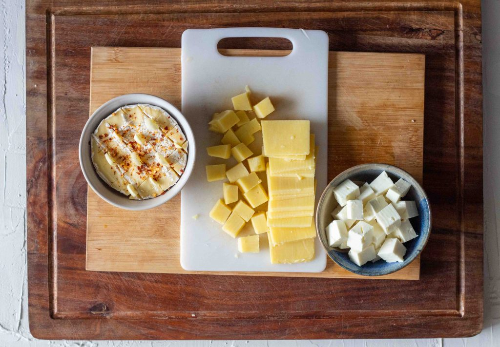 Cheese set out for a cheese board. From left to right there is brie with garlic and chilli flakes in a bowl, followed by cubed and sliced cheddar, and then cubed feta cheese.