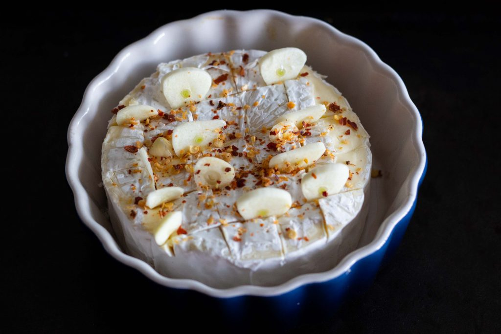 A round of brie cheese with sliced garlic and red chili flakes in an oven safe blue dish.