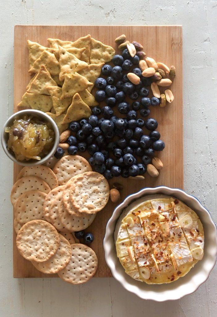 A cheese board with crackers, blueberries, mango chutney along with baked brie with garlic and chili.
