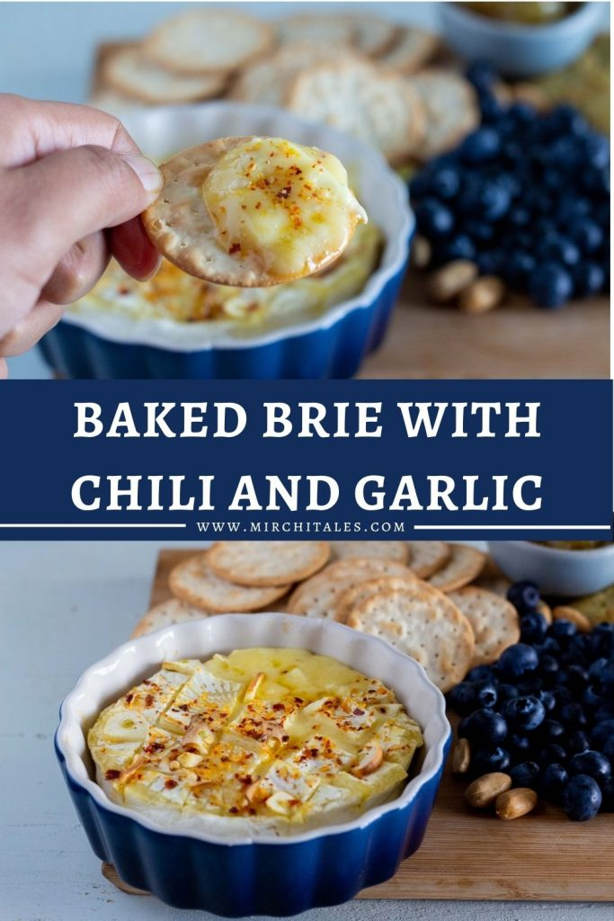 Baked brie with garlic and chili in a cheese board which has blueberries, crackers and nuts.