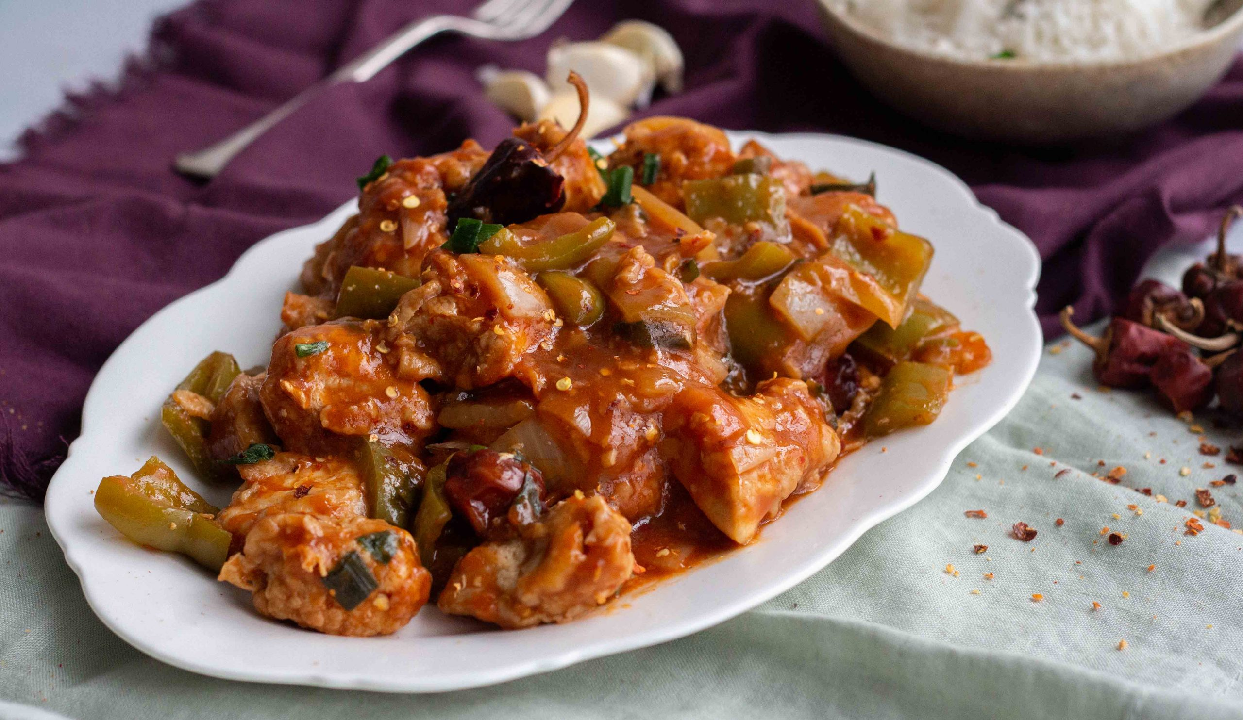 Indo Chinese style chicken manchurian served on a white platter with rice in the background.