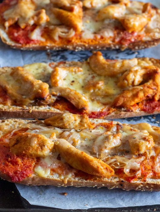 Three slices of chicken tikka bread pizza on a baking tray. The bread pizza is topped with grilled chicken flavored with chicken tikka spices, onions, tomato sauce and cheese.