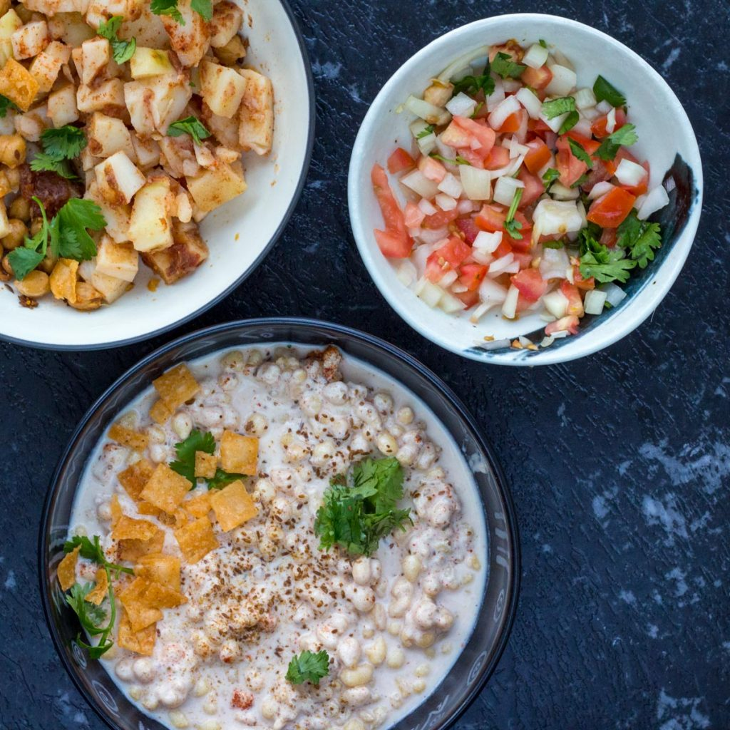 Three bowls filled with ingredients for chaat. Top left is a bowl filled with chickpeas. Top right is a bowl filled with diced up tomatoes and onions. On the bottom is a bowl filled with dahi boondi (lentil fritters) in yoghurt topped with crispy paapri and coriander.