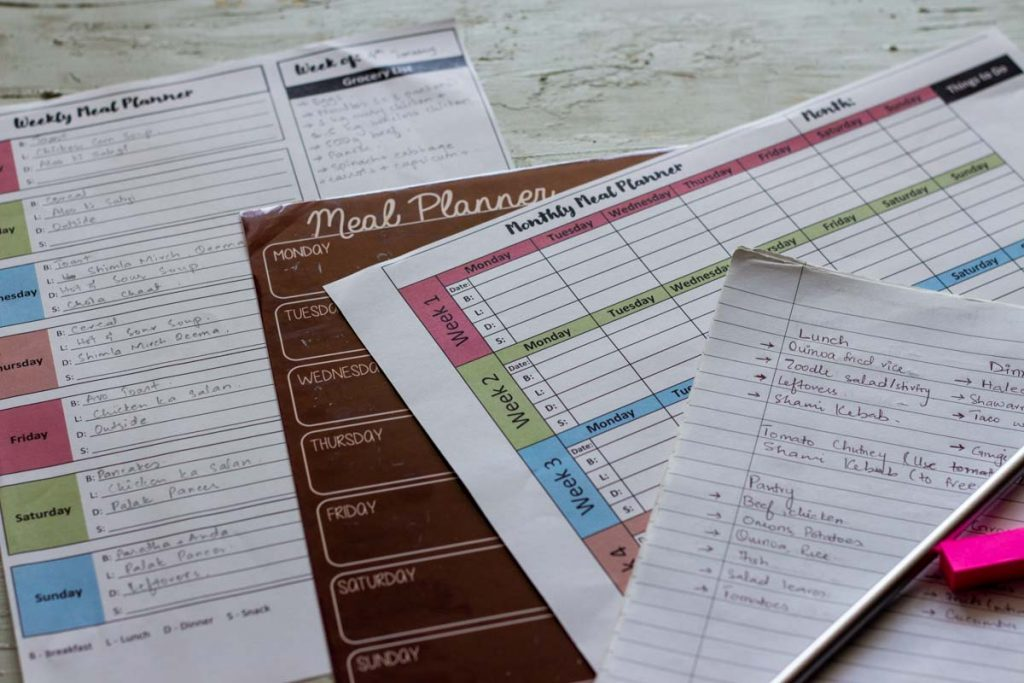 Different types of templates for meal planning. From left to right is a printed weekly meal plan template, then a magnetic weekly meal plan template, and then a monthly meal plan template and then a diary.