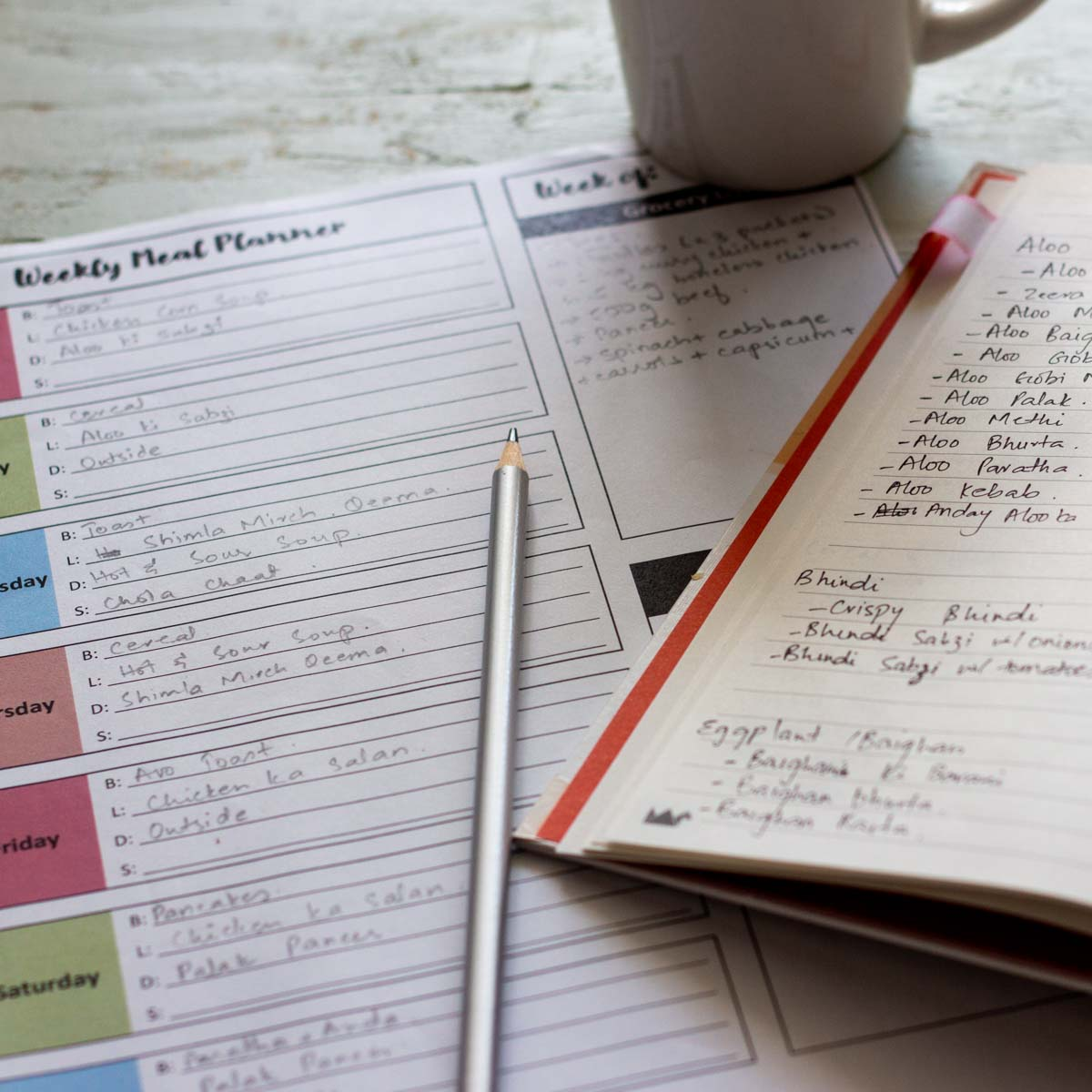 A printed weekly meal plan with a pencil on the plan. Next to the plan is a corner of a diary listing vegetarian dishes. On the top of the diary is a corner shot of a cup of tea.