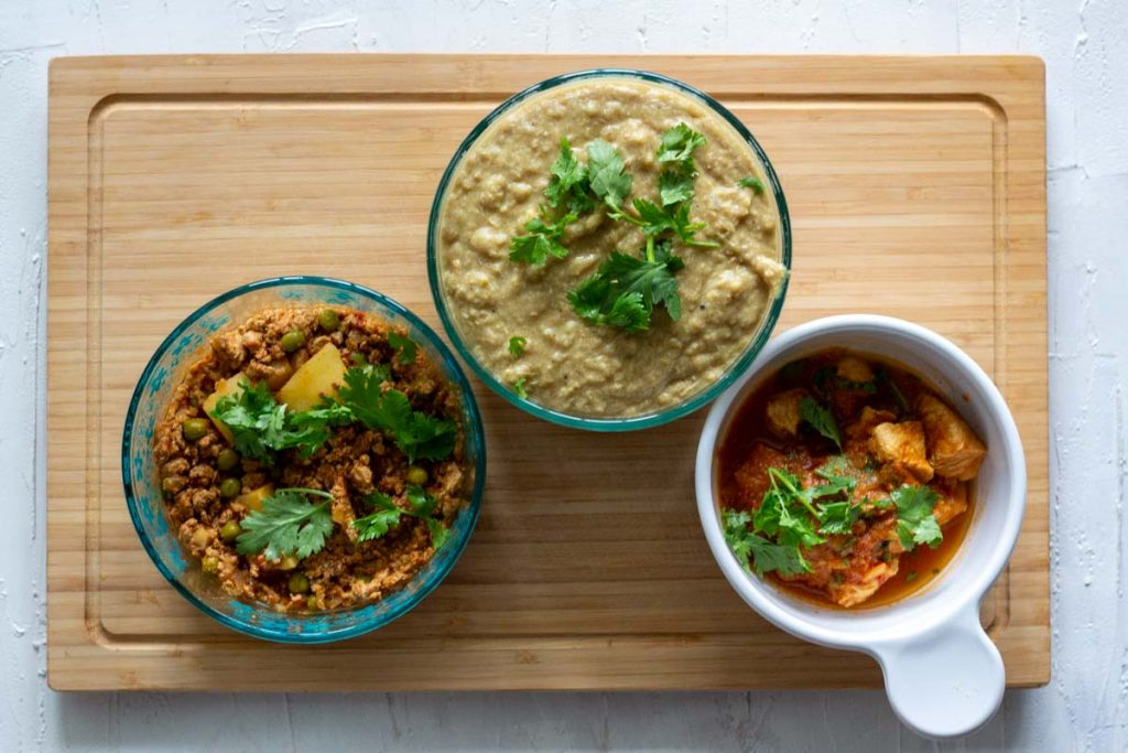 Three bowls placed on a light coloured wooden chopping board. Extreme left is a bowl of aloo keema (potato and mince curry). In the middle is haleem (meat and lentil stew) and on the right is a bowl of ginger chicken.