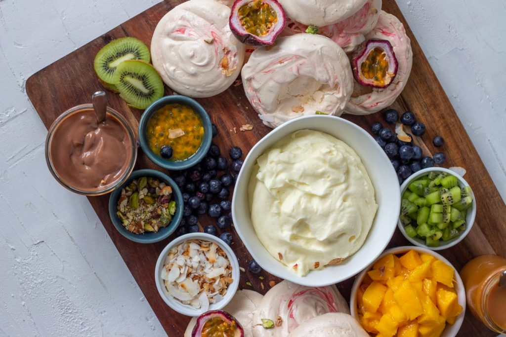 A pavlova grazing platter  at an angle on a wooden chopping board. There are mini pavlovas, chopped mangoes, diced kiwifruit, passionfruit, blueberries, toasted coconut flakes, along with salted caramel sauce and chocolate ganache.