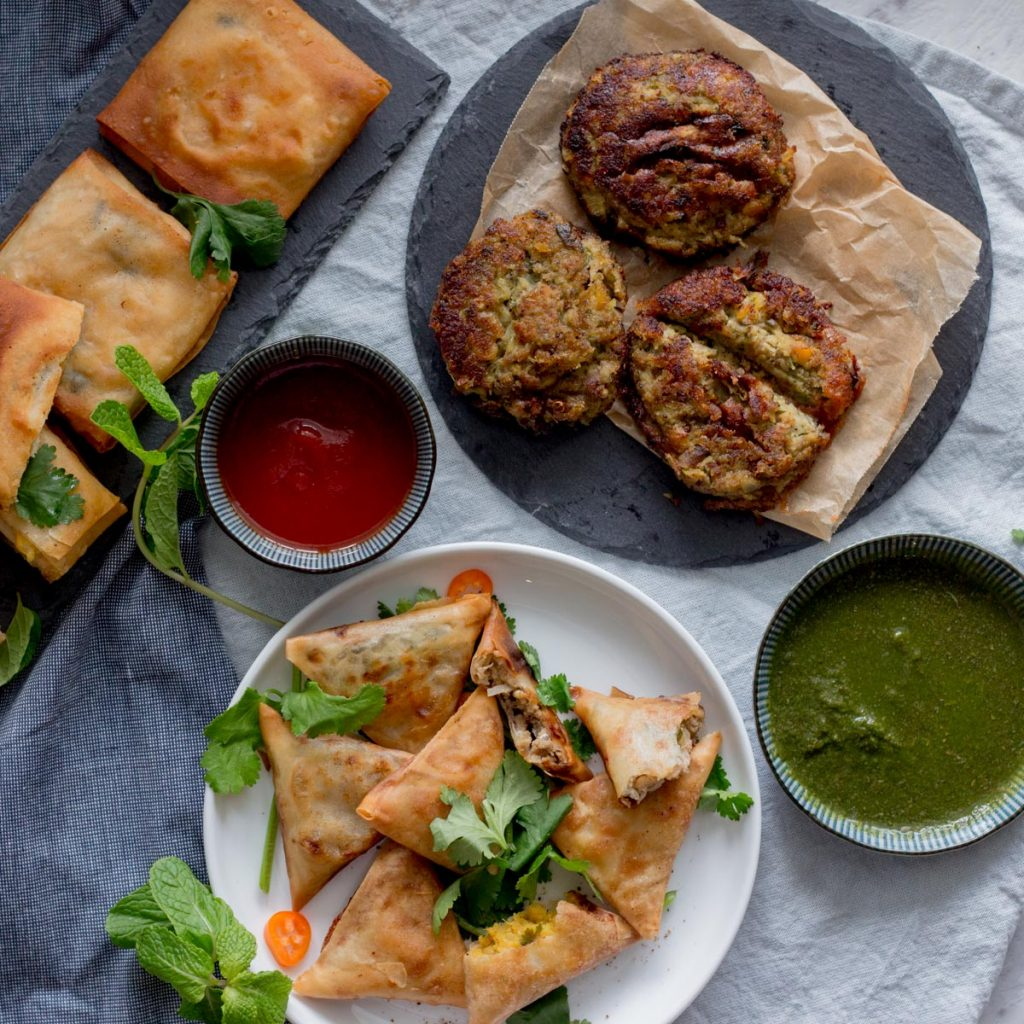 A plate of keema samosas (mince samosas), with green chutney on the side. On top of the green chutney is a black slate plate with three shami kebabs (lentil and meat kebabs) with a bowl of tomato ketchup next to it. On the top left are chicken box patties.