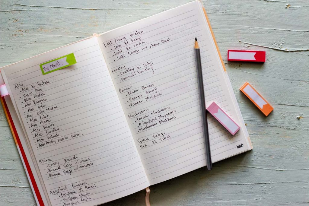 A recipe master list for meal planning. A diary listing names of vegetarian recipes on both sides of the page. On top of the diary is a pencil, and three pieces of sticky notes.