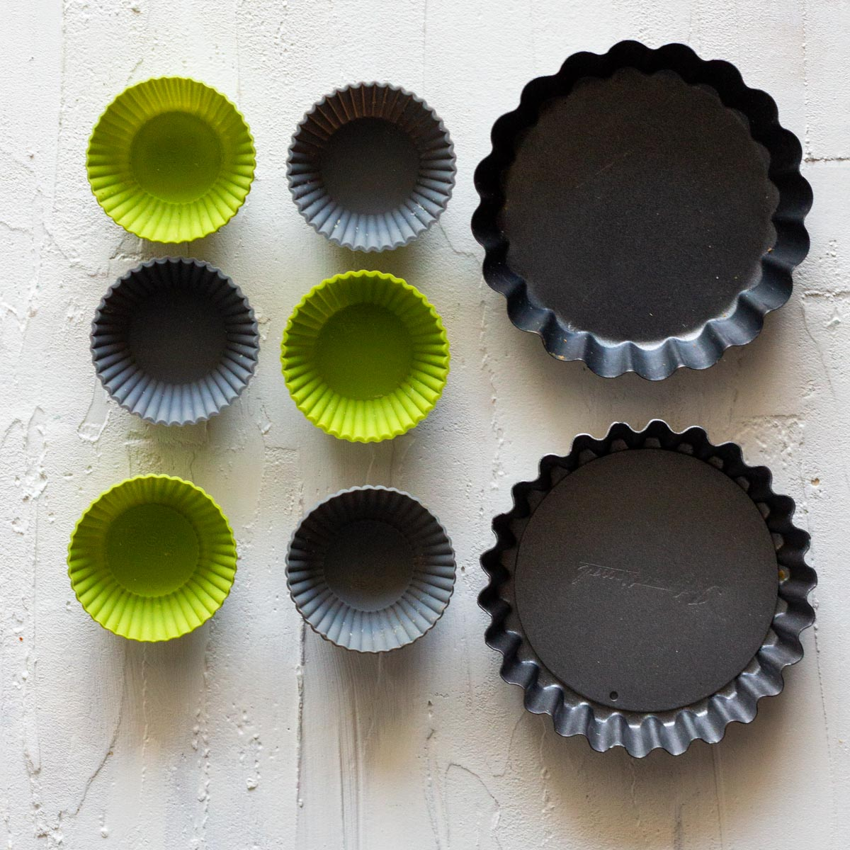 6 silicon baking molds in green and grey color on the left. Next to the silicon molds are non-stick baking molds.