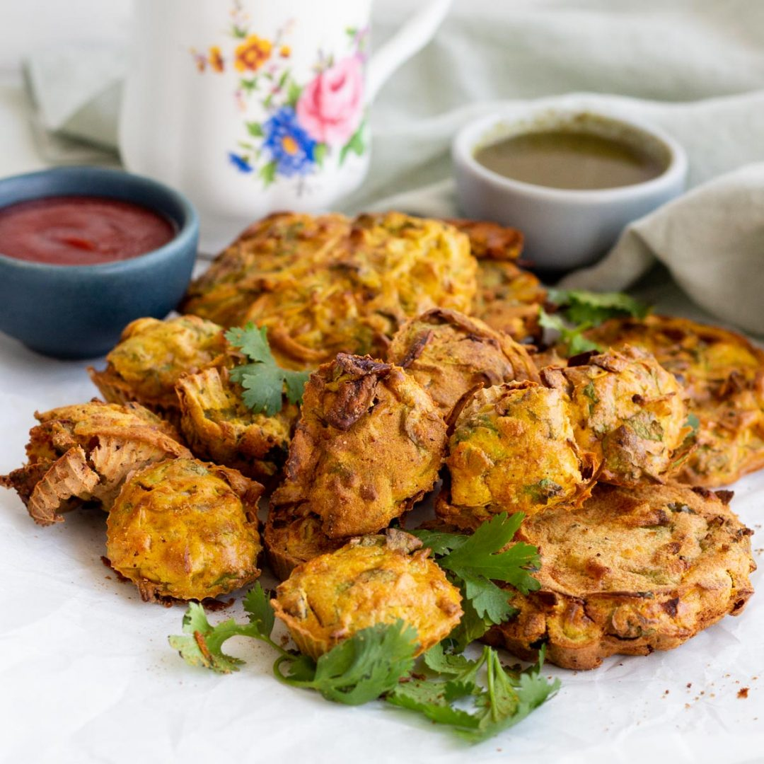 A mound of air fryer pakoras with coriander on top. Behind the air fryer pakoras is green chili sauce, and tomato ketchup.