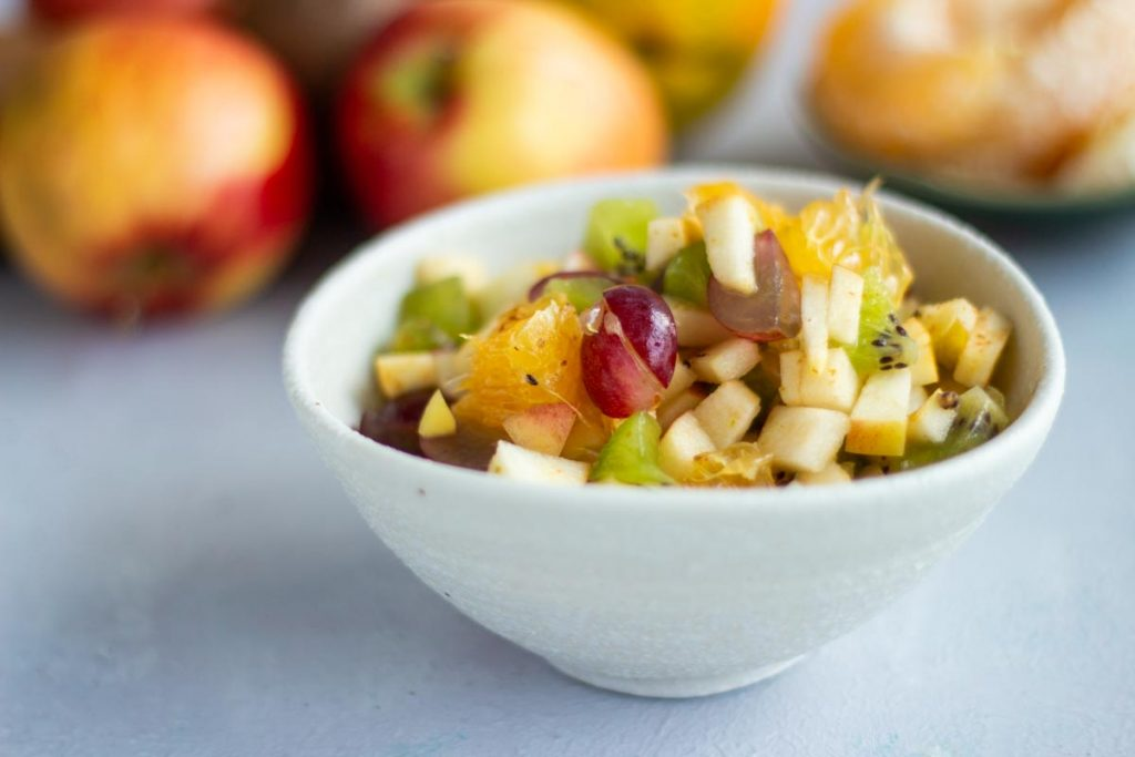 A bowl of fruit chaat containing diced apples, diced oranges, diced grapes, and diced kiwifruit in a white bowl on a white background.