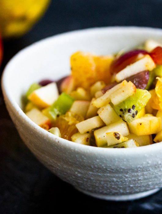 A bowl of fruit chaat containing diced apples, diced oranges, diced grapes, and diced kiwifruit in a white bowl on a black background.