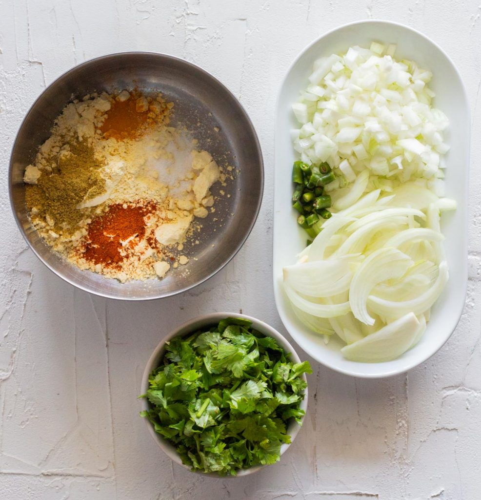 Ingredients for air fryer pakoras - chopped coriander leaves in a small bowl and a large bowl of chickpea flour / besan with red chili powder, salt, coriander powder and turmeric. There is also a plate of sliced onions, chopped onions and green chilies.