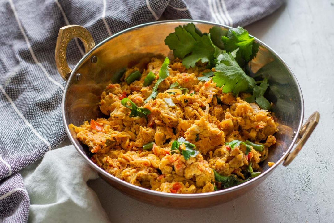 Khagina or Pakistani style scrambled eggs in a silver serving bowl with bronze handles. The khagina is topped with coriander leaves.