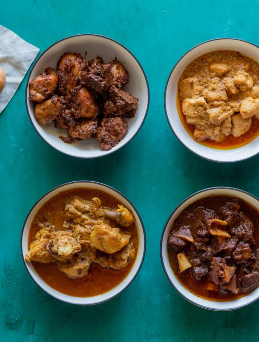 Four white bowls with blue rims. Clockwise from the top is dry chicken curry, boneless chicken curry (chicken ka salan), goat meat / mutton ka salan, and then bone in chicken ka salan.