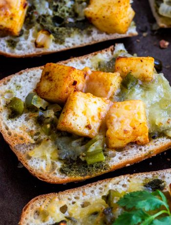 Three paneer toast sandwiches cut in half, laid out on a black baking tray.
