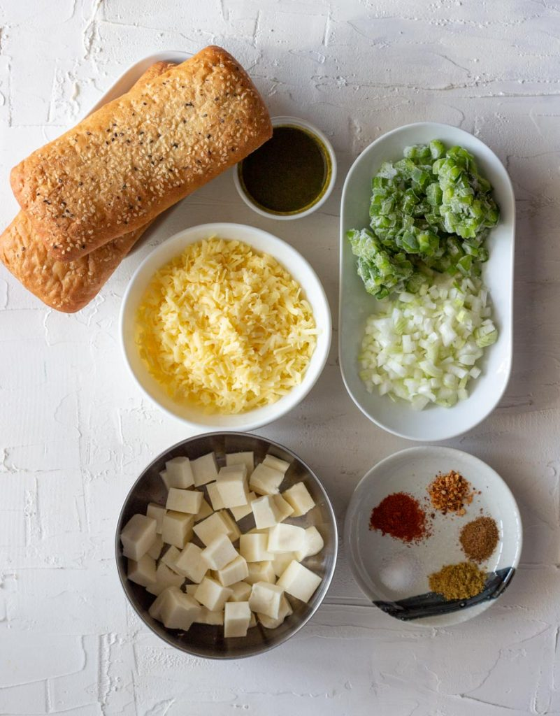 Ingredients laid out for paneer tikka sandwich on a white board. From top left, there are two turkish bread rolls, green chutney, diced capiscum / green bell pepper and diced onions, spices, cubed paneer / Indian cottage cheese and shredded cheese