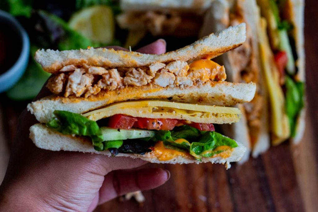 A person holding up a chicken club sandwich so that the cross section is visible. There is bread, chicken, sriracha mayonnaise, sliced cucumber, sliced tomato, cheese and lettuce.