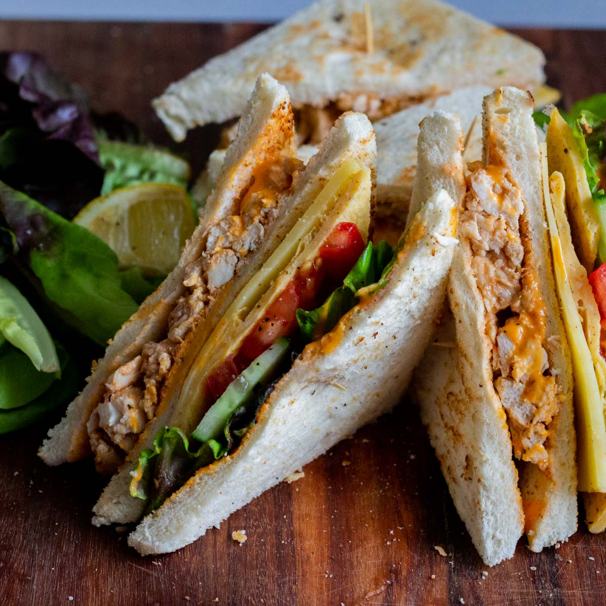 There are two chicken club sandwiches on a wooden chopping board. On the back of the sandwiches is lettuce, along with a lemon wedge.