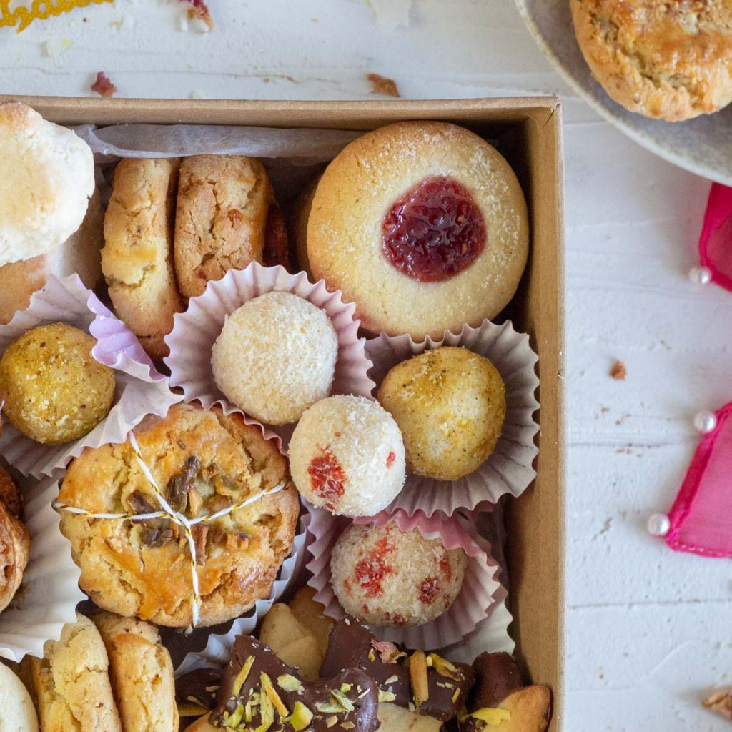 A shot of the top right corner of a box of Eid cookies. The cookies include thumbprint jam cookies, coconut laddos, nan khatai, and cardamom shortbread with chocolate and pistachios.