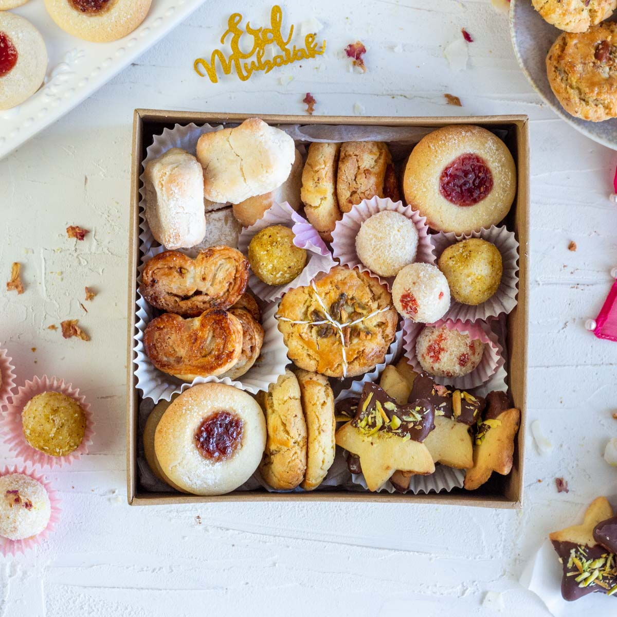 An Eid cookie box with an assortment of cookies. Clockwise from top left are Italian almond cookies, nan khatai, thumbprint jam cookies, coconut laddo, cardamom shortbread cookies with dark chocolate and pistachio, nan khatai and cinnamon palmers with nuts.