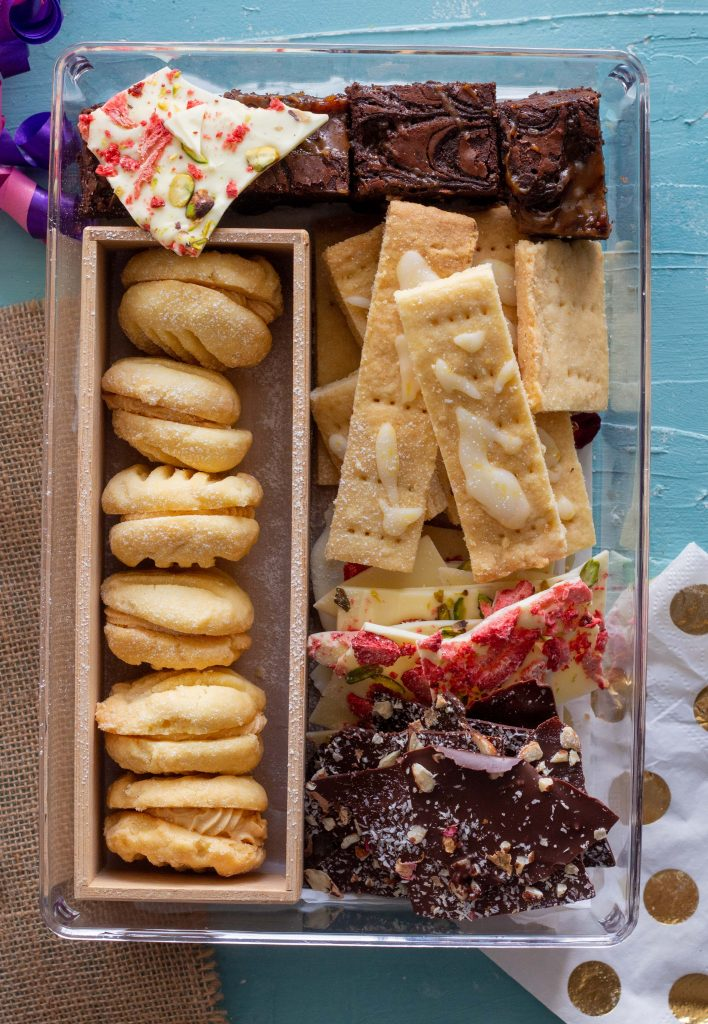 Eid cookie box featuring salted caramel melting moments, chocolate caramel brownies, lemon and cardamom shortbread, along with dark chocolate and white chocolate bark.