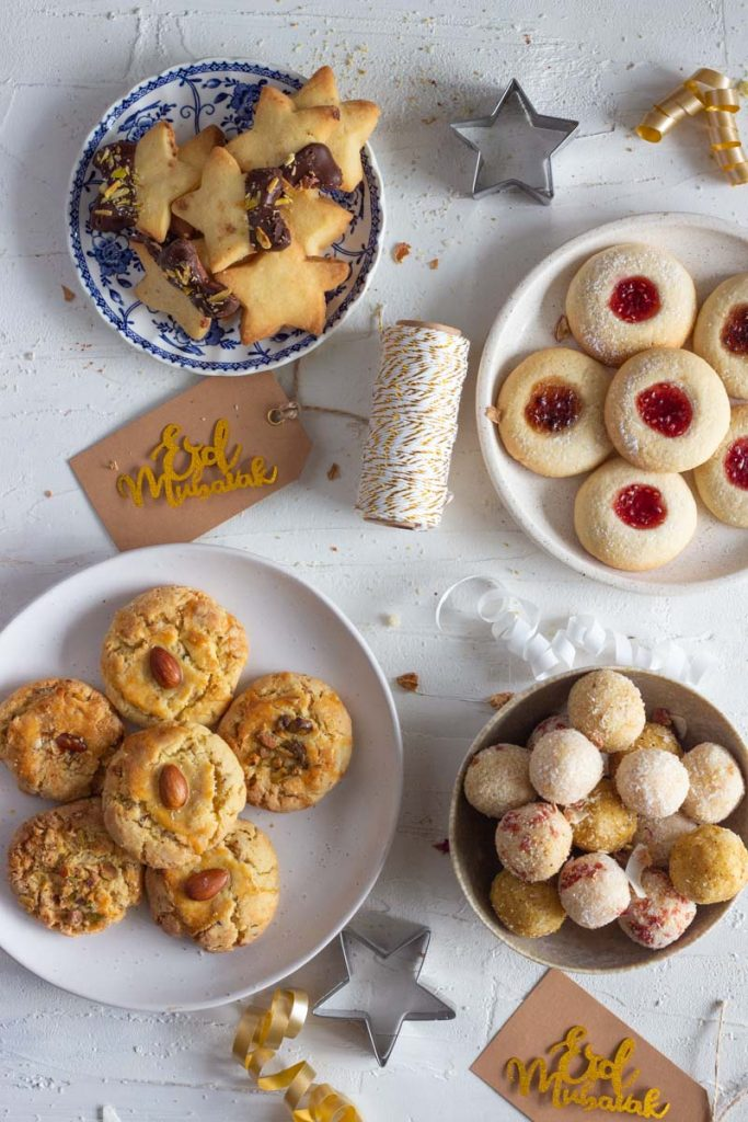 On the top left is a blue and white plate with star shaped cardamom shortbread cookies with chocolate and pistachios On the top right is a white plate with thumbprint jam cookies with plum jam and strawberry jam. On the bottom right is a small bowl with coconut laddos topped with pistachio, coconut and freeze dried strawberries. On the bottom left is a plate with nan khatai. In the middle are tags is a coil of ribbon, and tags with Eid Mubarak tags.