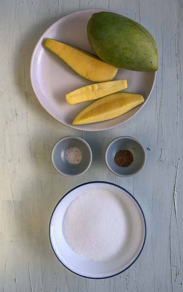 A white plate with a green mango, and three wedges of raw green mango. Below that are two mini bowls, one with roasted cumin powder, and one with black salt. On the bottom is a bowl of white sugar.