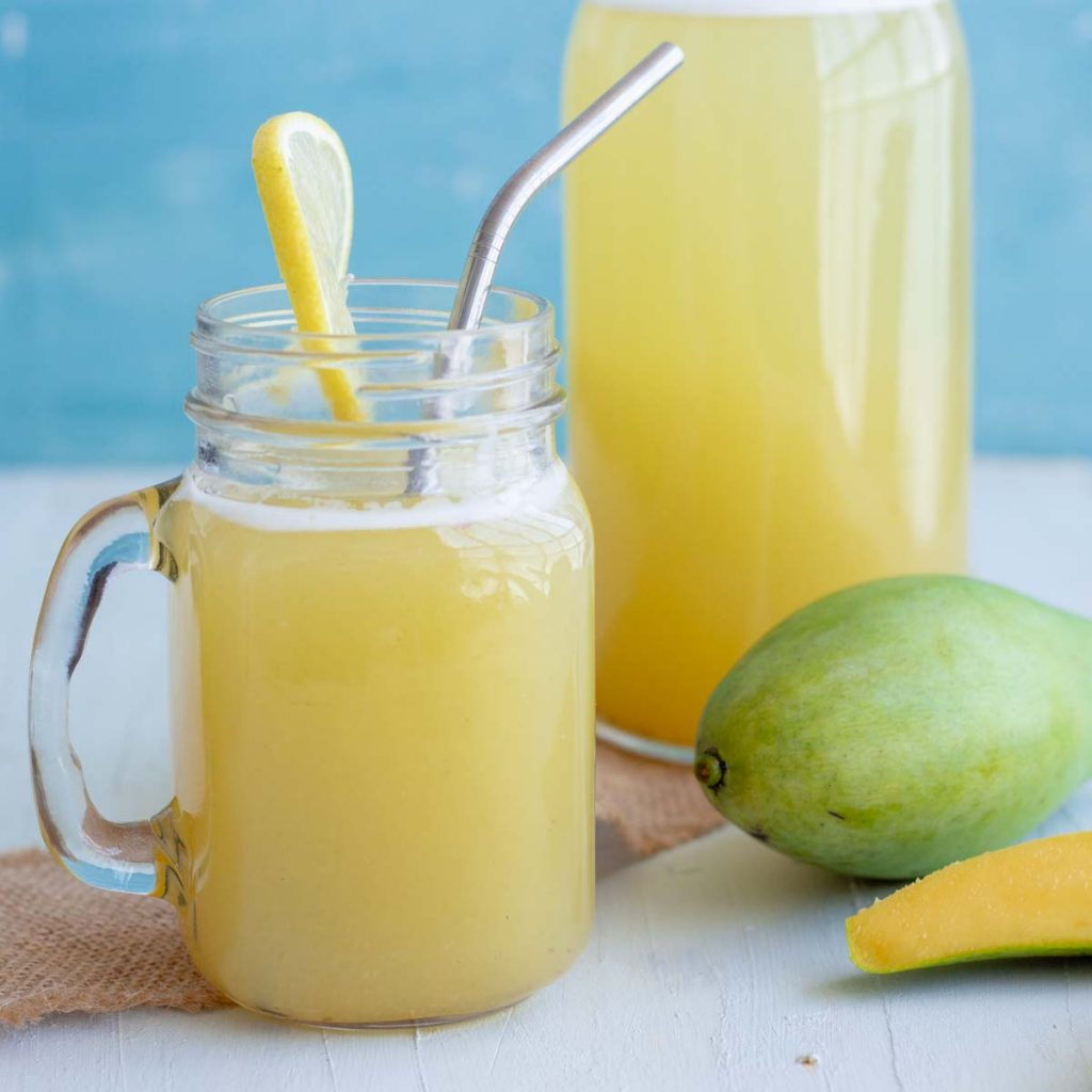 A mason jar with aam panna or green mango drink with a slice of lemon, and a stainless steel straw in it. Behind the mason jar is a bottle filled with aam panna, and a raw green mango.
