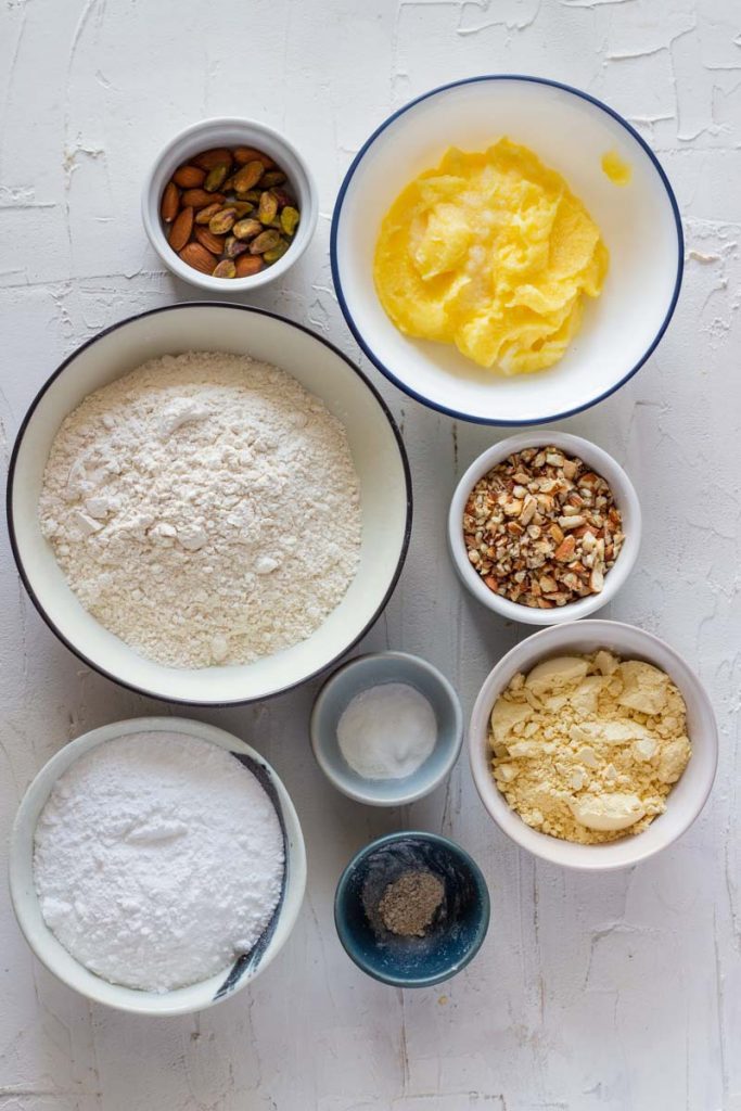 Ingredients for nan khatai. Clockwise from top are almonds and pistachips in a small bowl, ghee in a bowl, roasted and crushed almonds, chickpea flour, cardamom flavor, sugar, baking powder and baking soda, and flour.