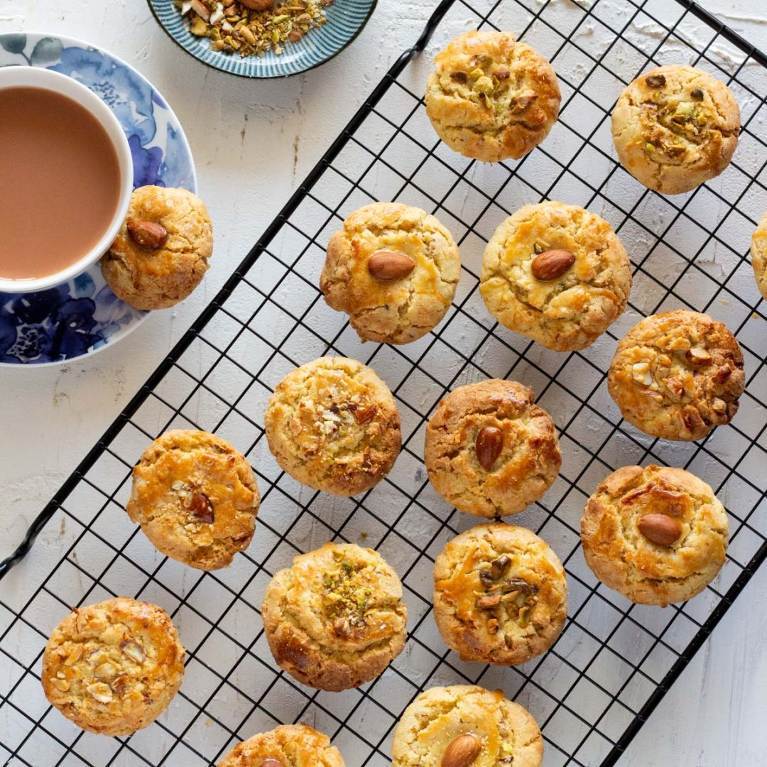 A cooling rack placed diagonally with nan khatai on top of it. On the top left is a small plate with crushed almonds and pistachios, and below that is a teacup and a saucer with a nan khatai biscuit placed on the saucer.