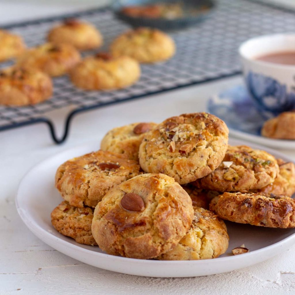 A plate of nan khatai in the front. On the back is a cooling rack with nan khatai on top of it, and a teacup with a saucer.