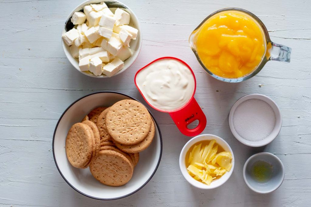 Ingredients for no bake mango cheesecake. From the top clockwise is diced cream cheese, cream, mango puree, sugar, lemon juice, butter and digestive biscuits.