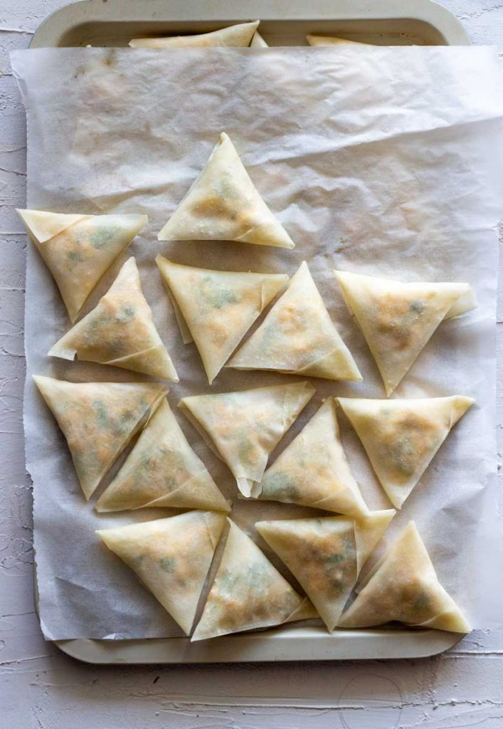 A tray topped with baking paper, and then topped with unfried paneer samosas. There are 5 lines of paneer samosas with 4 samosas per line.