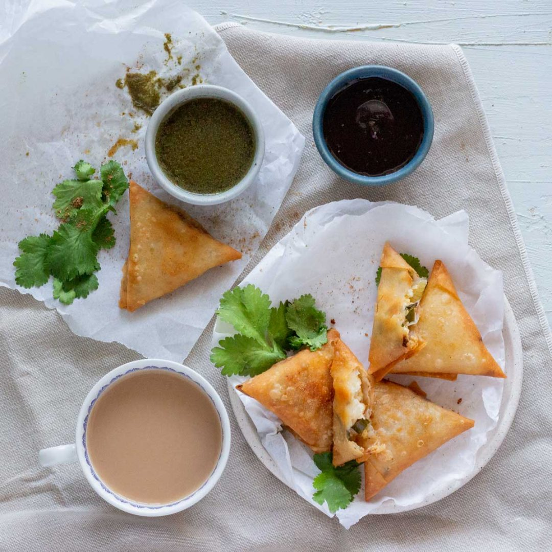 A white plate with 4 paneer samosas, and one of the samosas is broken in half to reveal the filling inside. On the left of the plate is a cup of tea. On the top is another paneer samosa, and a small bowl of green chutney, and tamarind chutney.