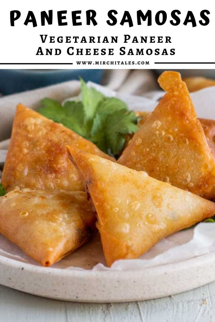 A white plate topped with parchment paper and 4 paneer samosas.