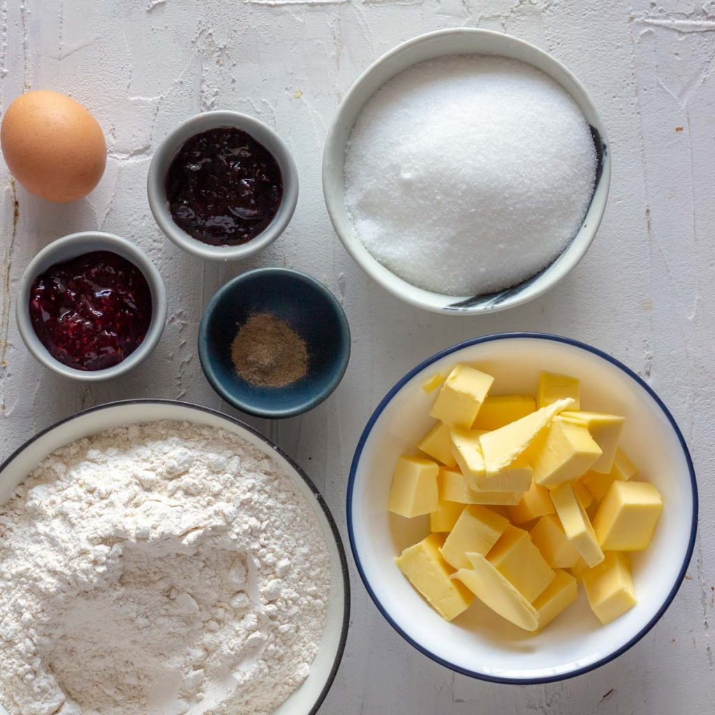 Ingredients for cardamom jam thumbprint cookies laid out. There is butter, flour, cardamom powder, blackberry jam, raspberry jam, an egg and sugar.