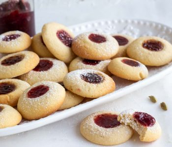 Cardamom Jam Thumbprint cookies in a white platter. In front of the platter are two jam cookies, and one has a bite in it. There are also two cardamom pods next to the cookies. On the back is a jar of raspberry jam.