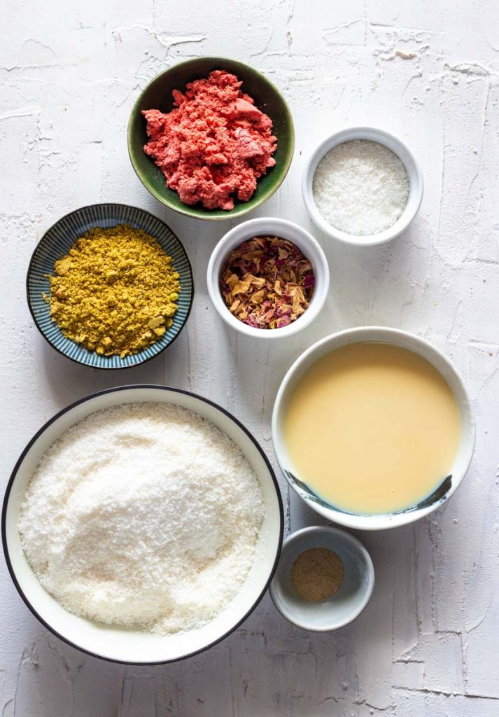 Ingredients for instant coconut ladoos (or cardamom coconut fudge balls). Ingredients clockwise from top are freeze dried strawberries, coconut, rose petals, condensed milk, cardamom powder, desiccated coconut and pistachio powder.