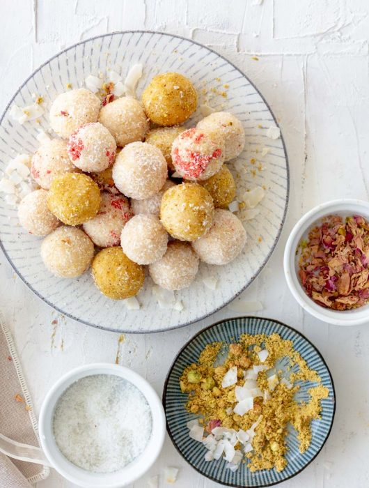 A variety of coconut ladoos placed in a circular heap in a plate. To the right of the plate are crushed rose petals in a small bowl. On the bottom is a plate with pistachio powder, and coconut flakes, as well as a small bowl with desiccated coconut. To the left of the plate is a ribbon, and a beige napkin.