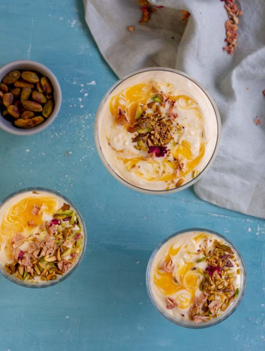 Three glasses of mango mousse on a blue background. The mango mousse cups are garnished with mango puree, pistachios and rose petals. On the top right corner is a napkin, and on the top left corner is a small bowl of pistachios.